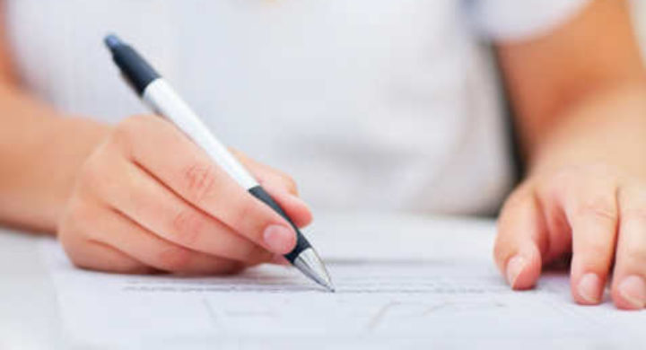 Closeup of a business woman signing an agreement, focus on her hands