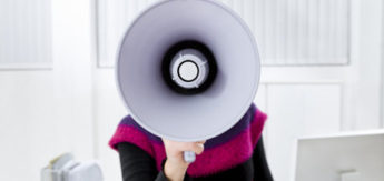 young businesswoman in office talking on the megaphone