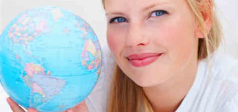 Closeup portrait of a charming young female smiling while holding a world globe
